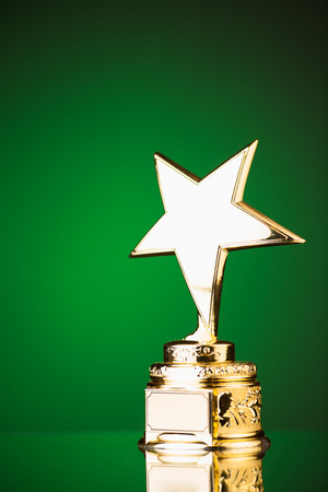 gold star trophy against green background