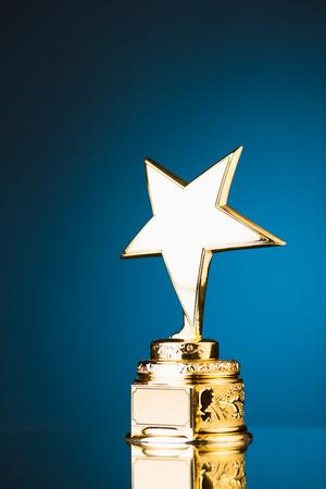 trofeo: trofeo de la estrella de oro sobre fondo azul Foto de archivo