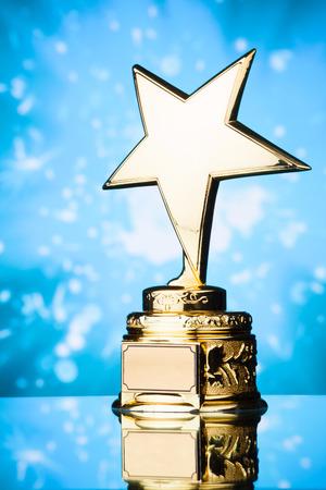 gold star trophy against blue sparks background 写真素材