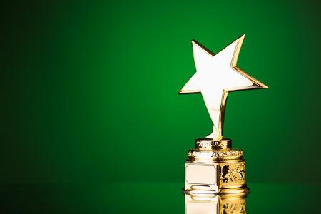 trofeo: trofeo de la estrella de oro sobre fondo verde Foto de archivo