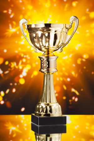 shiny gold: gold cup trophy against shiny sparks background