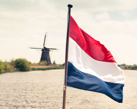 netherlands: Flag of the Netherlands against windmill background Stock Photo