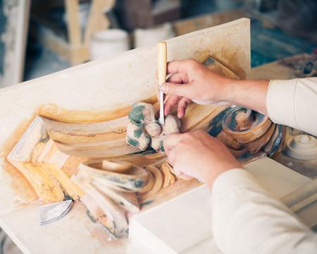 handen van de restaurateur werken met antieke decor element