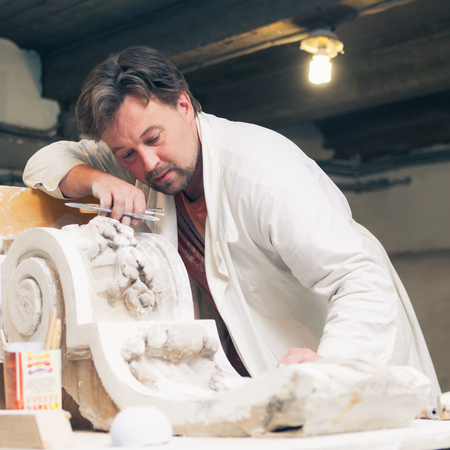 restorer working with gypsum model at workshop photo