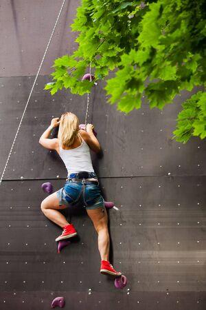 climbing: woman climbing artificial rock wall