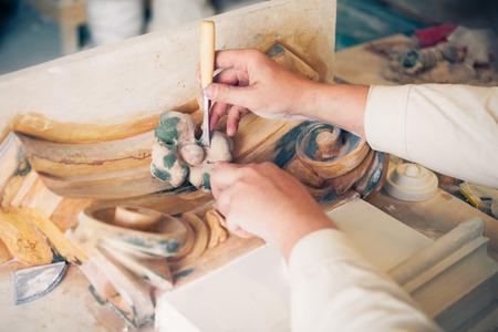 refurbish: hands of restorer working with antique decor element