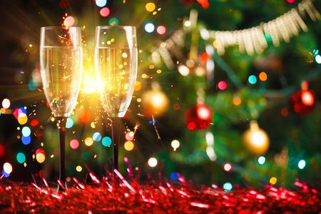慶典: 對香檳酒杯和焰火,聖誕樹裝飾品為背景 版權商用圖片