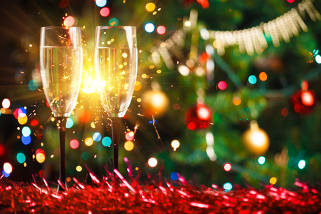 brindisi champagne: paio di bicchieri di champagne e spumante, albero di Natale ornamento come sfondo