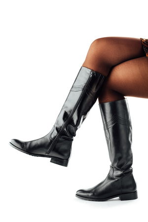 women in boots: woman legs wearing black leather high boots, isolated on white Stock Photo