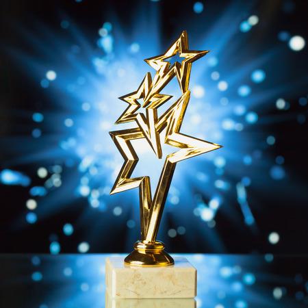 shiny gold: gold stars trophy against shiny sparks background Stock Photo