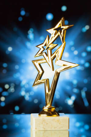 blue metal: gold stars trophy against shiny sparks background Stock Photo