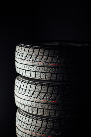vulcanization: studless winter tires stack, black background Stock Photo