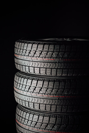 winter tires: studless winter tires stack, black background Stock Photo