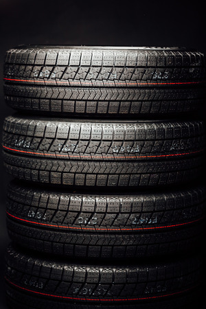 studless winter tires stack, black background Stock Photo