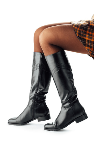 botas: piernas de la mujer llevando altas botas de cuero negro, aisladas en blanco Foto de archivo
