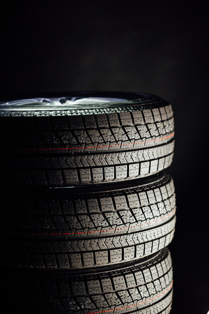 aluminum wheels: studless winter tires stack, black background Stock Photo