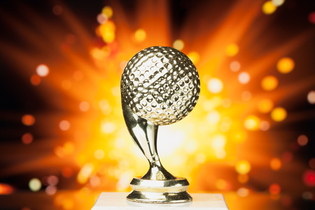 trophies: golf ball trophy against shiny sparks background