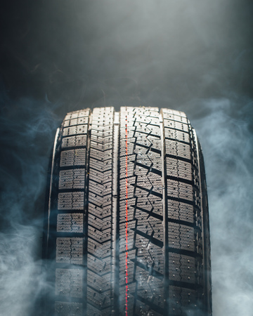 tire: winter tire in smoke, closeup view