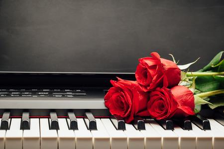 rode rozen op piano toetsen met exemplaar-ruimte Stockfoto