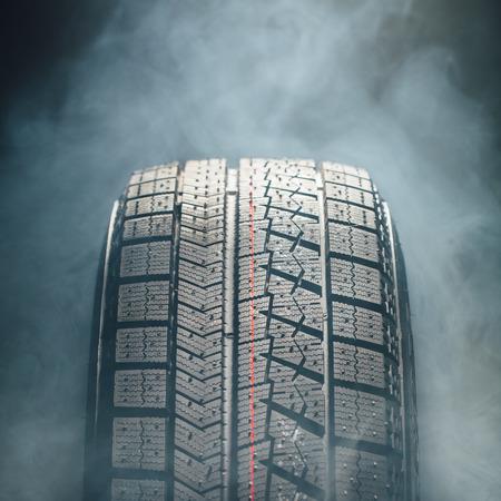 vulcanization: winter tire in smoke, closeup view