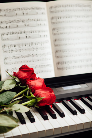 music book: red roses on piano keys and music book