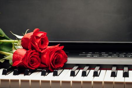 klawiatura: klawisze fortepianu i czerwona róża z kopiowaniem miejsca