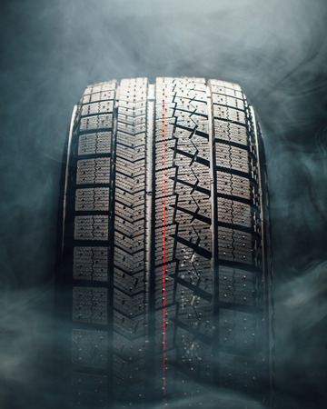 winter tire: winter tire in smoke, closeup view