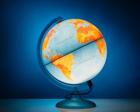 illuminated: illuminated earth globe model on blue background Stock Photo
