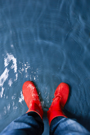 rain wet: red rubber boots in the water