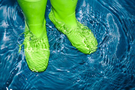 uniform green shoe: green rubber boots in the water Stock Photo