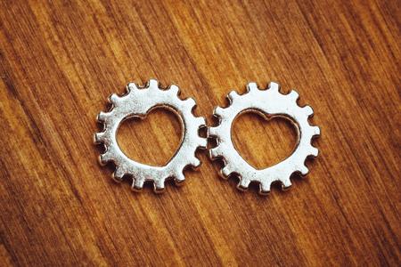 heart gear: gear wheels with heart symbol, wooden background