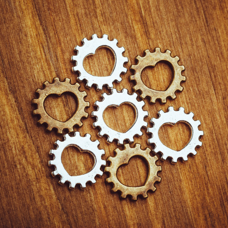 gear symbol: gear wheels with heart symbol, wooden background