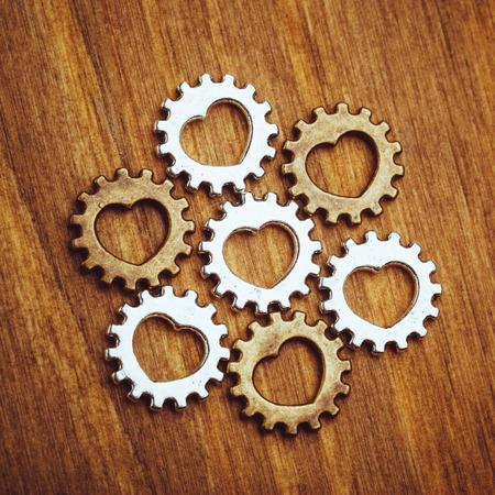 Zahnräder mit Herz-Symbol, Holzuntergrund