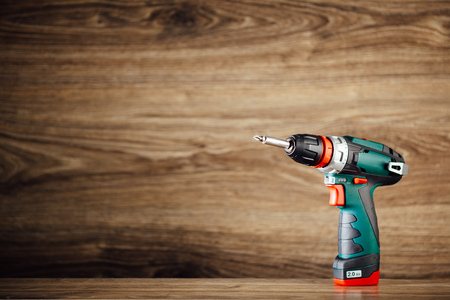 cordless: cordless screwdriver against wooden background
