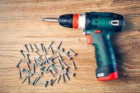 fasteners: screws fasteners and electric screwdriver on wooden background Stock Photo