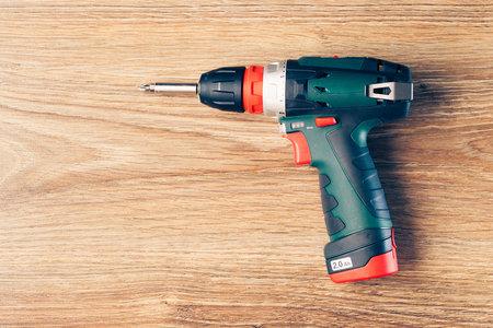 taladro: atornillador a batería contra el fondo de madera