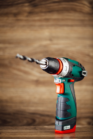 drill floor: cordless drill against wooden background