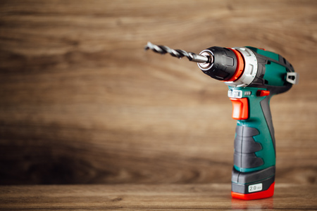 a drill: electric drill against wooden background