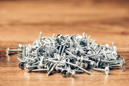 fasteners: screws fasteners hardware heap on wooden background Stock Photo