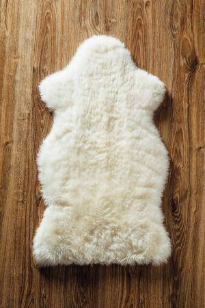 sheepskin: sheepskin carpet on wooden background Stock Photo