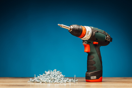 fasteners: cordless screwdriver and fasteners screws on blue background
