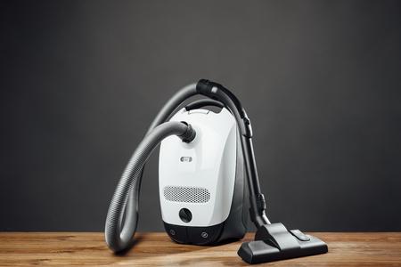 personal de limpieza: aspiradora sobre fondo gris Foto de archivo