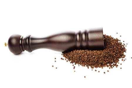 pepper grinder: pepper mill on peppercorns heap, isolated on white