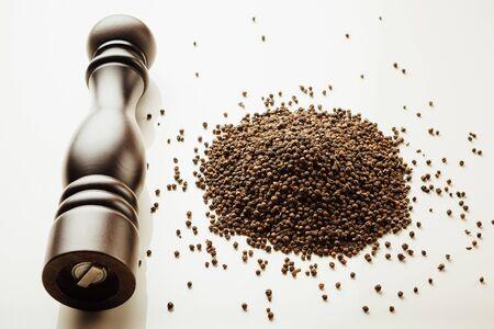 seasoning: pepper mill and peppercorns heap, white background Stock Photo