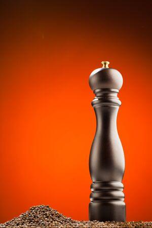 Pfeffermühle und Pfeffer Haufen, orange Hintergrund