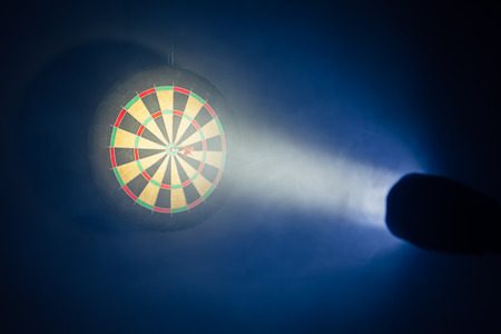 business game: darts board illuminated with a spotlight Stock Photo
