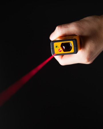 distance: laser distance meter in hand, black background