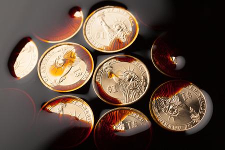 monedas de dólar en el petróleo crudo - concepto de precio del barril Foto de archivo