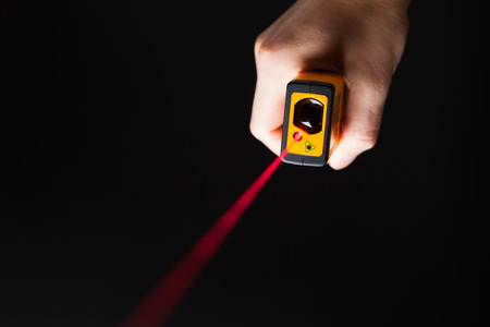 laser distance meter in hand, black background