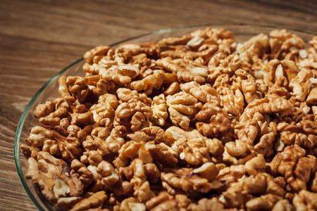 shelled: shelled walnuts on a plate, wooden background Stock Photo